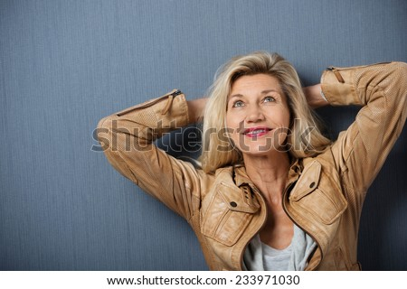 Attractive mature woman standing thinking with her hands behind her head leaning on a dark background looking into the air with a smile - stock photo
