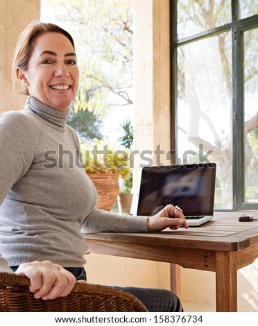 Attractive mature woman using her laptop computer while sitting in at home near large glass windows and a green garden, joyfully turning and smiling at camera. - stock photo