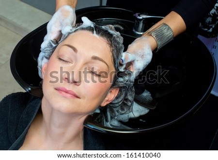 attractive mature woman washing her hair in salon