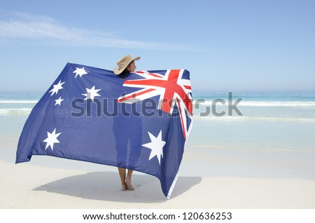 Attractive mature woman wearing akubra hat and with Australian flag around shoulder standing at tropical Australian beach, isolated with ocean and blue sky as background and copy space.