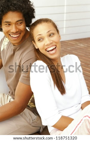 Attractive merry young ethnic couple having a good laugh while seated back to back on a brick patio - stock photo