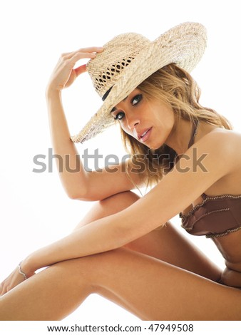 attractive mid adult woman in swim wear, holding straw hat and looking at camera on white background. Vertical shape - stock photo