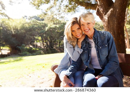 attractive mid age mother and daughter sitting on a bench outdoors - stock photo