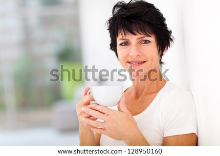 attractive mid age woman enjoying coffee at home - stock photo