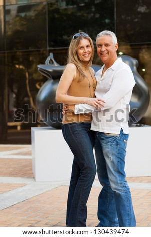 Attractive middle age couple outdoors in a downtown urban setting. - stock photo