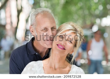 Attractive middle-age couple posing for a portrait with their heads close together in a tree lined urban street