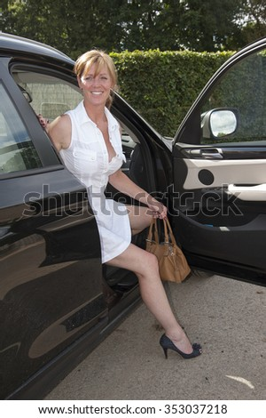 Attractive middle aged blond woman with brown handbag getting out of a car