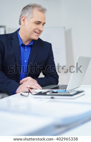 Attractive middle-aged businessman sitting at his desk in the office reading his laptop screen with a quiet smile of satisfaction, profile view