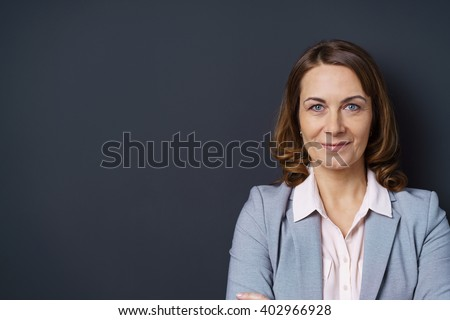 Attractive middle-aged businesswoman with a confident friendly smile posing with folded arms against a dark background with copy space - stock photo