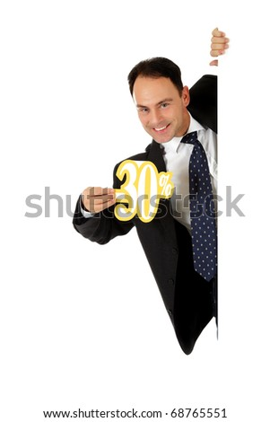 Attractive middle aged caucasian businessman behind a wall showing thirty percent discount sign. Copy space. Studio shot. White background.