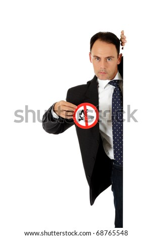 """Attractive middle aged caucasian businessman behind wall showing """"no fire in area"""" warning sign. Copy space. Studio shot. White background. - stock photo"""