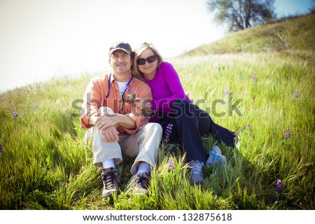 Attractive Middle aged couple lying in the tall grass and Wild Lupine - stock photo