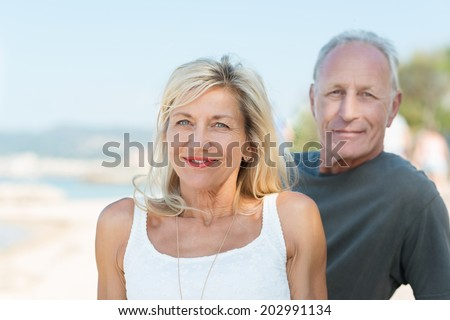 Attractive middle-aged couple on summer vacation at the seaside posing together on the beach smiling at the camera - stock photo