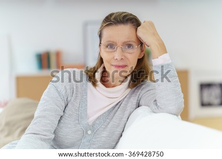 Attractive middle-aged housewife wearing glasses relaxing at home on a comfortable sofa in her living room smiling at the camera - stock photo