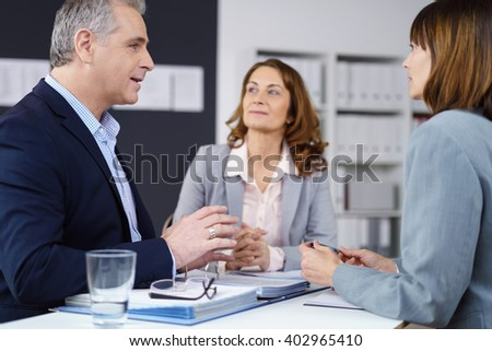 Attractive middle-aged male team leader brainstorming with his business team seated around a table in the office having a serious discussion - stock photo