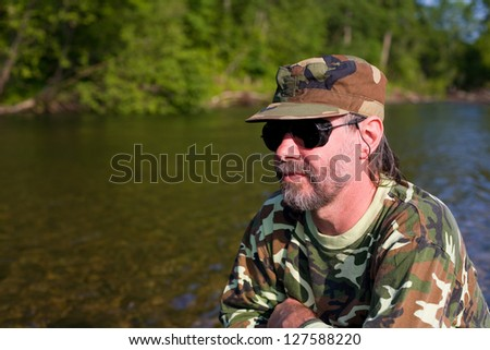 Attractive middle aged man at the river vacation. - stock photo