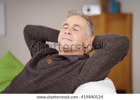 Attractive middle-aged man relaxing at home reclining on a comfortable sofa with his hands behind his head and eyes closed in pleasure - stock photo