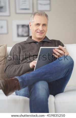 Attractive middle-aged man relaxing at home sitting on a comfortable sofa with his tablet computer smiling at the camera - stock photo