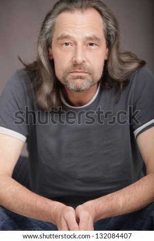 Attractive middle-aged man with a beard and long hair sitting in a chair facing the camera with a serious expression