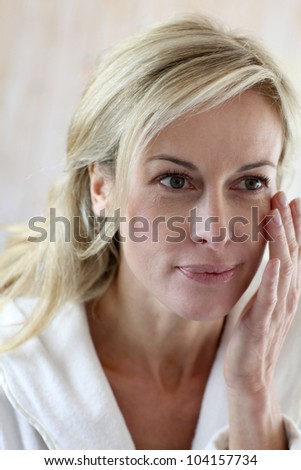 Attractive middle-aged woman applying comestics on her face - stock photo