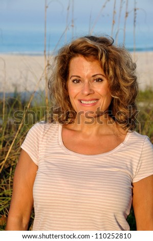 Attractive Middle Aged Woman enjoying the early morning sun at the beach - stock photo