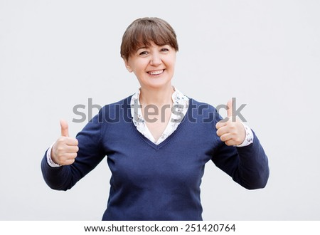 Attractive middle-aged woman giving a thumbs up sign - stock photo