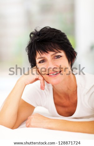 attractive middle aged woman lying on bed at home - stock photo