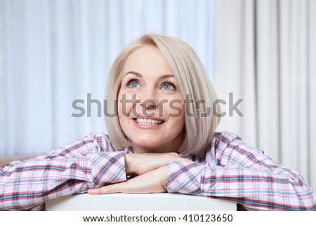 Attractive middle aged woman relaxing at home. The beautiful face close up. - stock photo