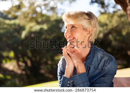 attractive middle aged woman sitting at the park - stock photo