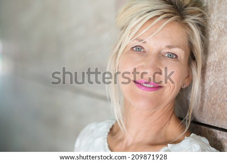 Attractive middle-aged woman with her blond hair tied loosely back looking at the camera with a gentle quiet smile as she leans against a receding wall with copyspace - stock photo