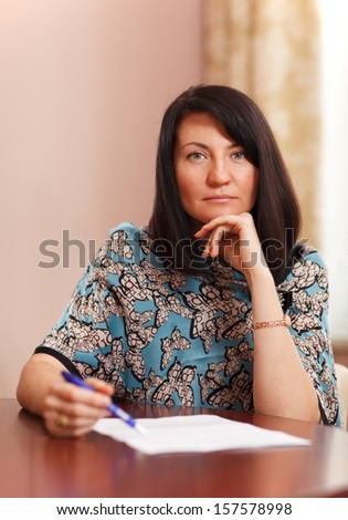 Attractive middle-aged woman working at home sitting at a table with a document in front of her and a pen in her hand looking thoughtfully at the camera - stock photo