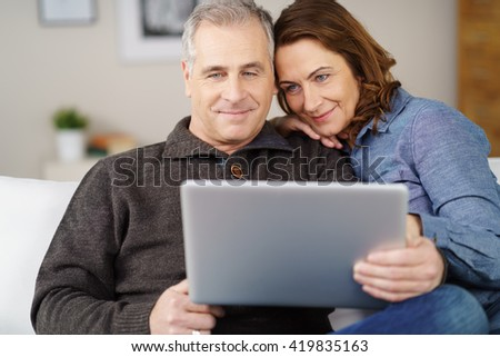 Attractive middle ahead male and female couple sitting close together on sofa while looking at open laptop computer with pleasant expression