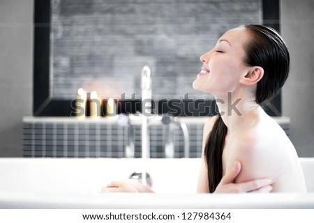 Attractive Mixed Asian Female smiling in the tub - stock photo