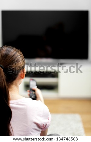 Attractive mixed female lifestyle watching tv - stock photo