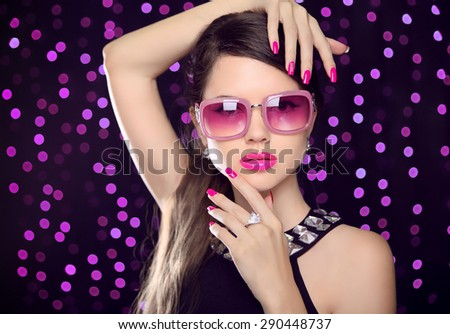Attractive Model with sunglasses. Beauty girl portrait with pink lips makeup, manicured polish nails and luxury gemstone necklace over party lights background.