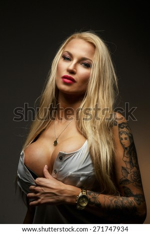 Attractive modern blond female with tattoo on her hand. Isolated on grey - stock photo