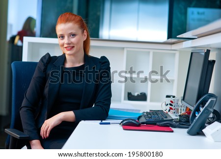 attractive modern businesswoman sitting and talking to phone in office cubicle workstation - stock photo