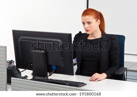 attractive modern red hair businesswoman  in small office cubicle workstation - stock photo