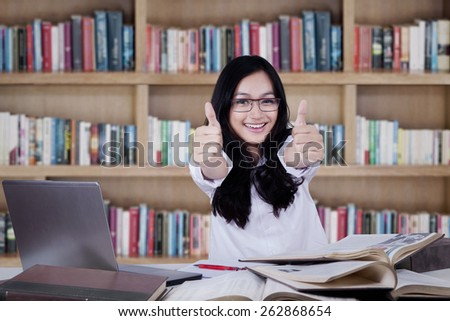 Attractive modern student studying in the library and showing thumbs up at the camera - stock photo