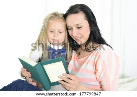 attractive mother and adorable blond daughter reading a book at home