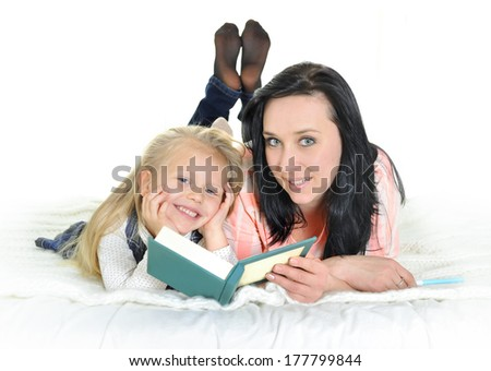 attractive mother and adorable blonde daughter reading a book at home - stock photo