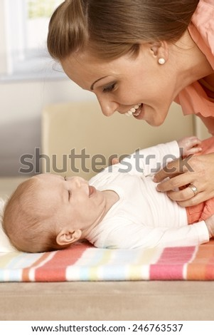 Attractive mother and baby laughing, having fun.