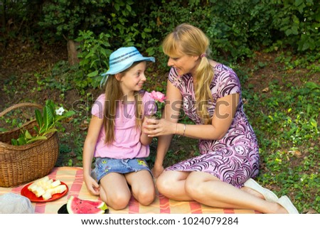 Attractive mother and cute little daughter with blue hat enjoying sweet watermelon during picnic time