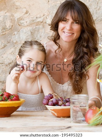 Attractive mother and young daughter sitting together at a holiday home table outdoors eating fresh fruits and enjoying a summer vacation. Family fun and healthy eating habits, travel and lifestyle.