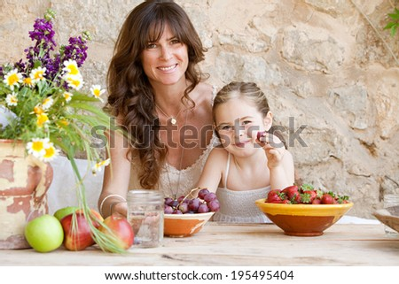 Attractive mother and young daughter sitting together at a holiday home table outdoors eating fresh fruits and enjoying a summer vacation. Family fun and healthy eating habits, travel and lifestyle. - stock photo