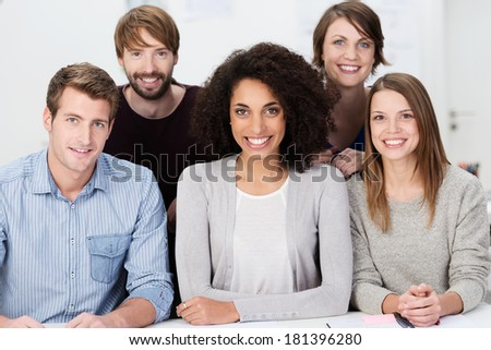 Attractive multiethnic group of young people posing grouped close together looking at the camera with warm friendly smiles - stock photo