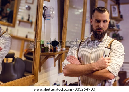 Attractive muscled bearded barber holding a hair trimmer and looking at camera while standing in the barber shop - stock photo