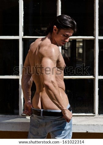 Attractive muscleman shirtless outdoors, partly showing ass - stock photo