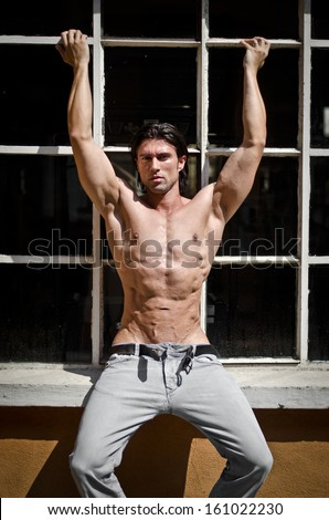 Attractive muscleman shirtless outdoors, sitting on window - stock photo
