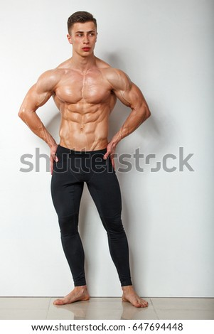 Attractive muscular body builder is posing in front of a white background